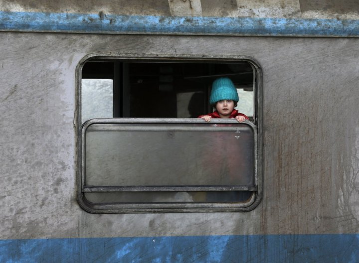 a-refugee-child-looks-out-of-a-train-window-at-a-train-station-in-the-town-of-sid-serbia-february-12-2016