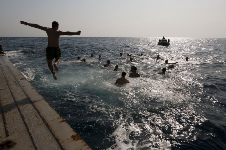a-sailor-jumps-off-the-stern-gate-of-the-uss-new-orleans-during-a-swim-call-in-the-gulf-of-aden