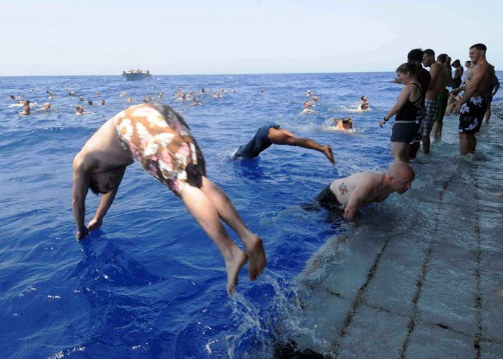 sailors-and-marines-aboard-the-multipurpose-amphibious-assault-ship-uss-bataan-dive-off-the-stern-gate-during-a-swim-call-in-the-mediterranean-sea