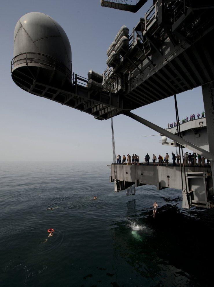 sailors-during-a-swim-call-jump-off-an-aircraft-elevator-aboard-the-nimitz-class-aircraft-carrier-uss-carl-vinson-into-the-arabian-sea